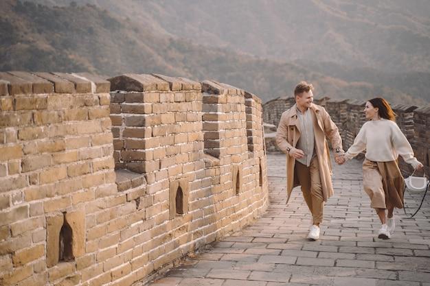 Jovem casal correndo e girando na grande muralha da china