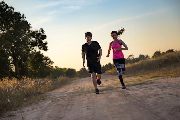 Jovem casal correndo na trilha da floresta