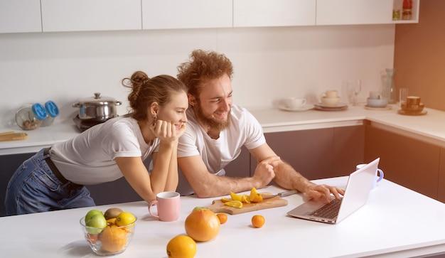 Jovem casal cozinhando alimentos saudáveis na cozinha em casa.