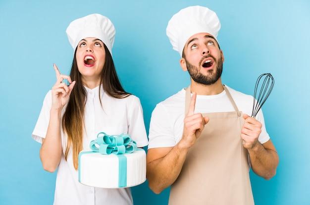 Jovem casal cozinhando um bolo isolado apontando para cima com a boca aberta.