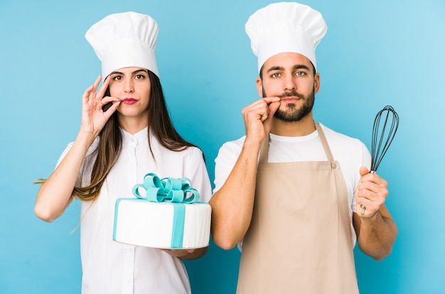 Jovem casal cozinhando um bolo isolado junto com os dedos nos lábios, mantendo um segredo.