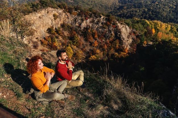 Jovem casal curtindo a natureza em um lindo dia ensolarado de outono. o casal está sentado em posição de lótus e meditando sobre o sol.