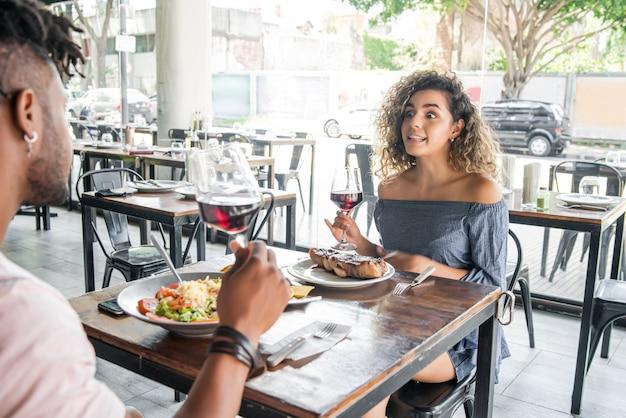 Jovem casal curtindo e passando bons momentos almoçando juntos em um restaurante. conceito de relacionamento.