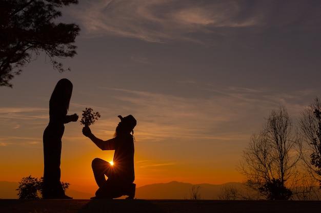 Jovem casal curtindo o pôr do sol na montanha
