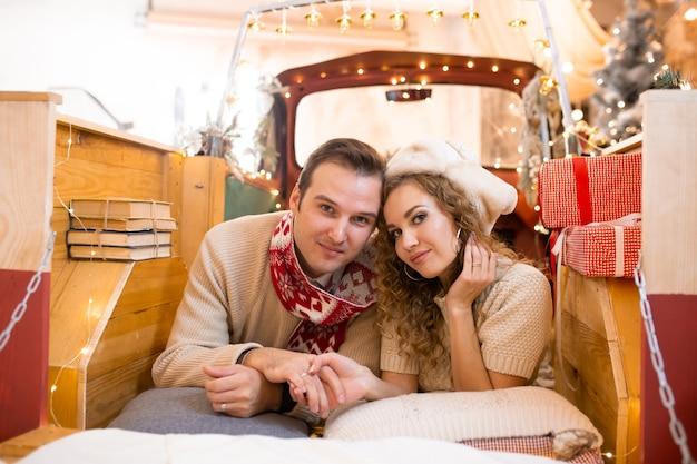 Jovem casal curtindo seu tempo juntos na pick-up. luzes de natal no fundo