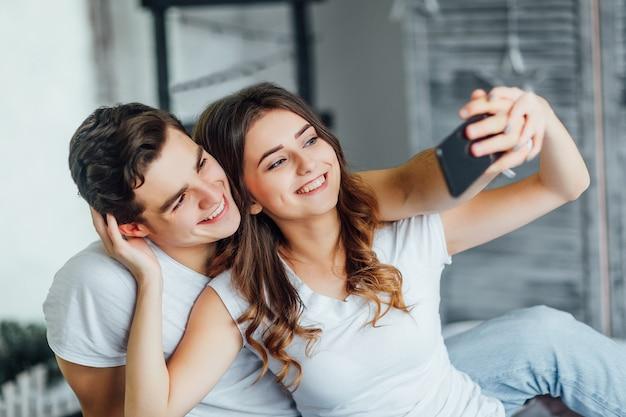 Jovem casal curtindo uma selfie juntos na cama pela manhã