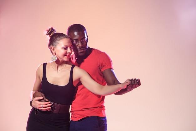 Jovem casal dança salsa caribenha social, estúdio filmado em fundo lilás. emoções humanas positivas. os modelos negros africanos e caucasianos