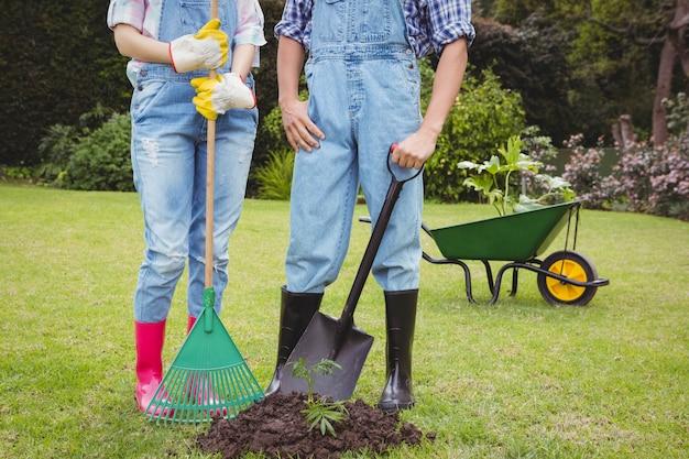 Jovem casal dançando com ancinho e pá perto de um rebento no jardim