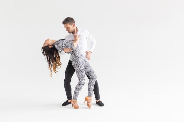 Jovem casal dançando dança latina bachata, merengue, salsa, kizomba. duas elegância posam sobre fundo branco com espaço de cópia