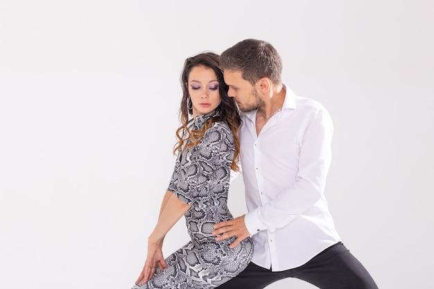 Jovem casal dançando dança latina bachata, merengue, salsa, kizomba. pose de elegância sobre parede branca com espaço de cópia