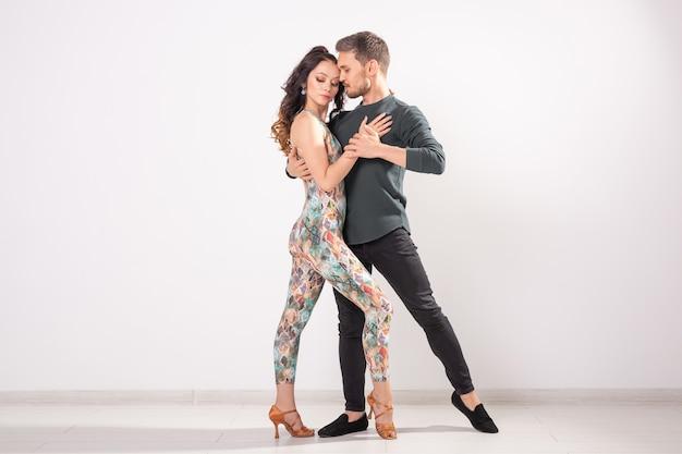 Jovem casal dançando dança social latina bachata, merengue, salsa. dois pose de elegância em fundo branco.