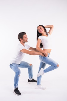 Jovem casal dançando dança social latina bachata, merengue, salsa. dois pose de elegância na parede branca.