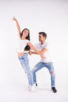 Jovem casal dançando dança social latina bachata, merengue, salsa. pose de elegância em branco