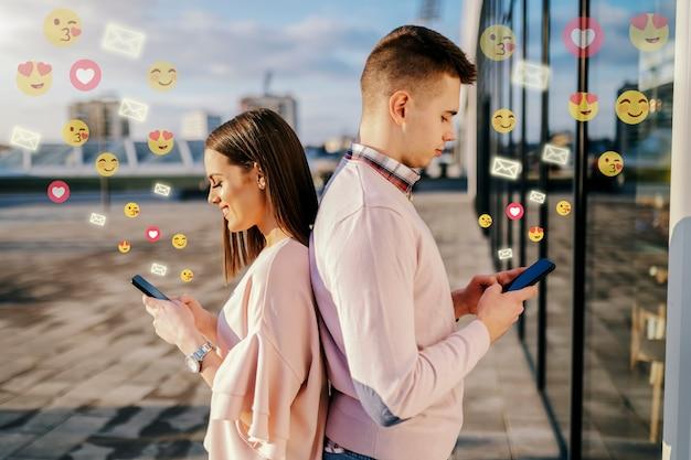 Jovem casal dançando de costas no telhado e usando telefones inteligentes para mídias sociais