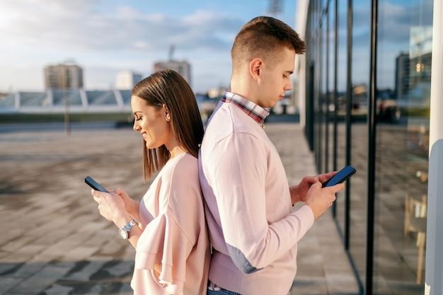 Jovem casal dançando de costas no telhado e usando telefones inteligentes