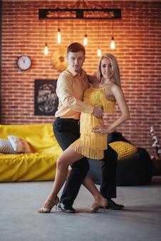 Jovem casal dançando música latina: bachata, merengue, salsa. pose de duas elegância no café com paredes de tijolo