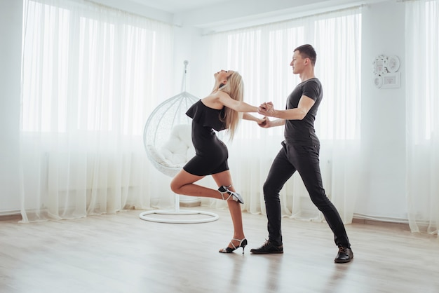 Jovem casal dançando música latina: bachata, merengue, salsa. pose de duas elegância no quarto branco