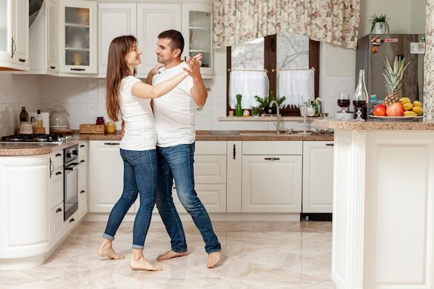 Jovem casal dançando na cozinha