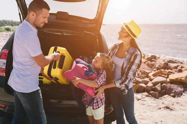 Jovem casal dançando perto da bota do carro aberto com malas e sacos. pai, mãe e filha estão viajando pelo mar ou pelo oceano ou pelo rio. passeio de verão de automóvel.