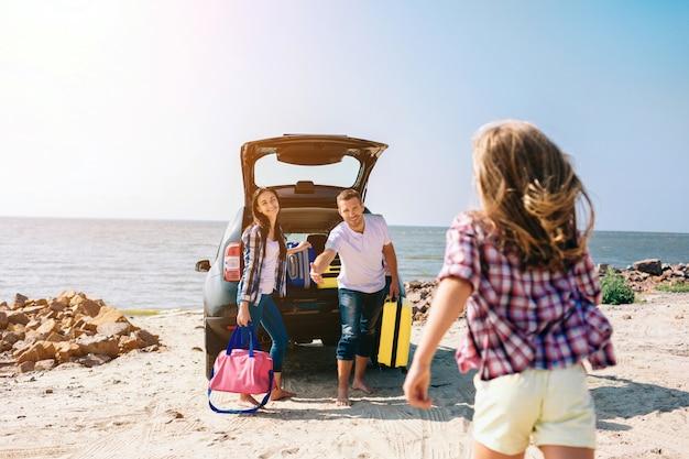 Jovem casal dançando perto da bota do carro aberto com malas e sacos. pai, mãe e filha estão viajando pelo mar ou pelo oceano ou pelo rio. passeio de verão de automóvel