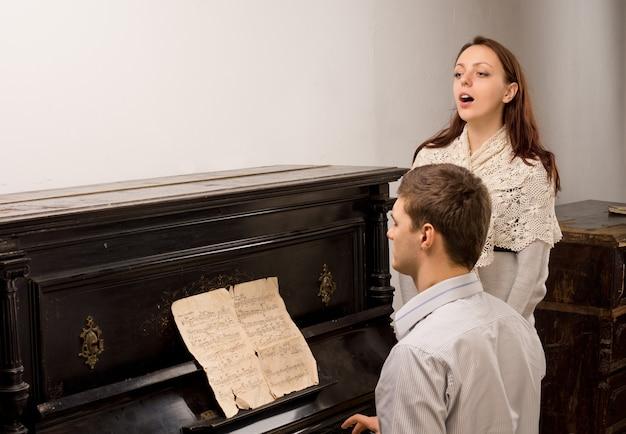Jovem casal dando um recital de canto com uma jovem e atraente vocalista