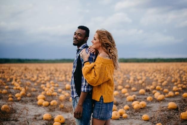 Jovem casal de agricultores feliz em um campo de abóboras