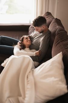 Jovem casal de alto ângulo relaxando no sofá
