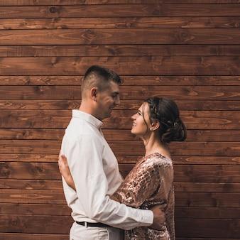 Jovem casal de amantes, homem e mulher em roupas da moda festivas, está abraçando. penteado casual leve para mulheres com permanente. fundo de prancha de madeira marrom