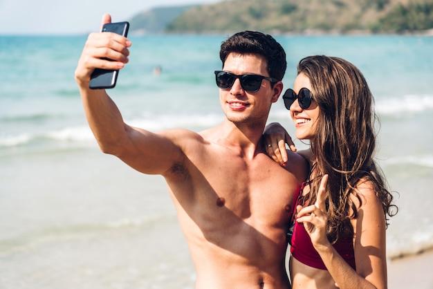 Jovem casal de amantes românticos relaxando juntos na praia tropical. homem e mulher tirando uma selfie com smartphone e curtindo a vida. férias de verão