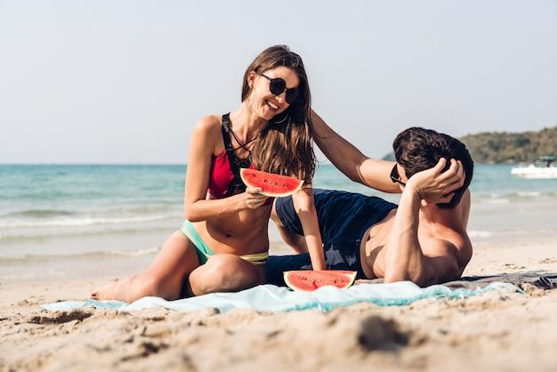 Jovem casal de amantes românticos relaxantes segurando e comendo uma fatia de melancia na praia tropical.