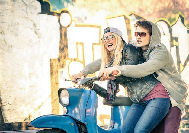Jovem casal de amantes se divertindo em uma moto scooter vintage