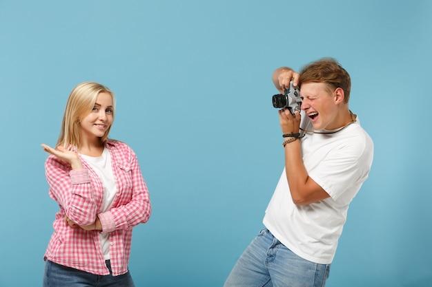 Jovem casal de amigos rapaz e mulher em camisetas brancas rosa vazias em branco posando
