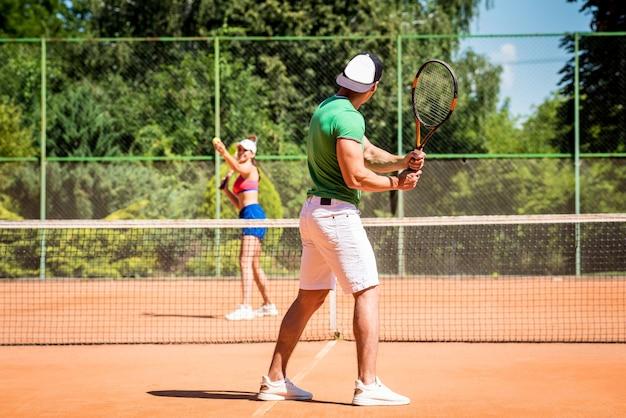 Jovem casal de atletas jogando tênis na quadra