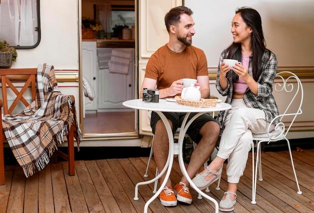 Jovem casal de aventureiros bebendo chá quente