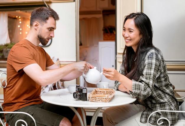 Jovem casal de aventureiros tomando uma xícara de chá ao lado da van