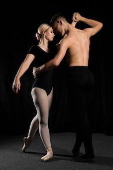 Jovem casal de balé posando em collant e calças justas