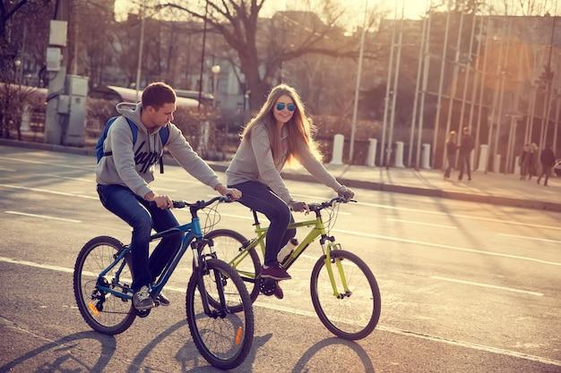Jovem casal de bicicleta na cidade ao pôr do sol