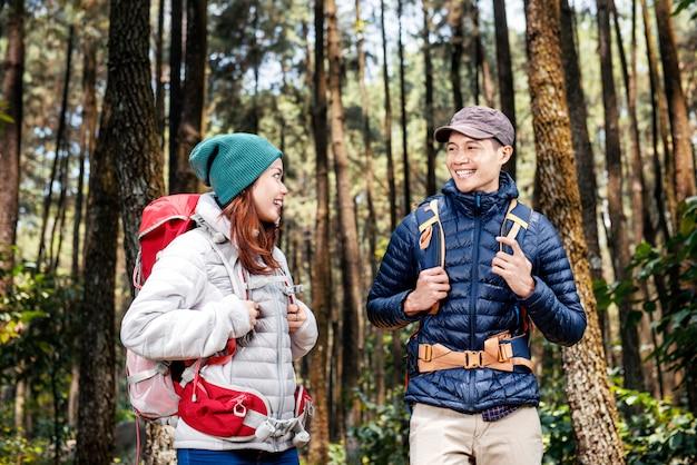 Jovem casal de caminhantes asiáticos com mochila de pé e olhando uns aos outros
