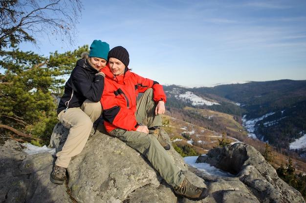 Jovem casal de caminhantes no topo da montanha