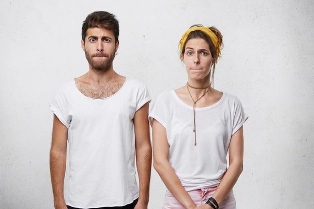 Jovem casal de camisetas brancas, perto um do outro, pressionando os lábios com desagrado de estar de mau humor