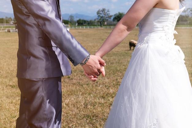 Jovem casal de casamento asiático noivo e noiva no jardim.