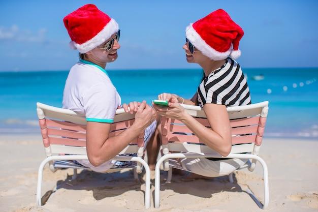 Jovem casal de chapéu de papai noel curtir férias de praia