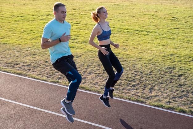 Jovem casal de desportistas em forma de menino e menina correndo ao fazer exercício em faixas vermelhas do estádio público ao ar livre.