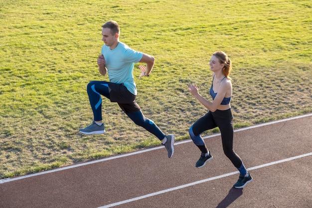 Jovem casal de desportistas em forma menino e menina correndo enquanto fazia exercício