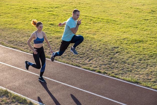 Jovem casal de desportistas em forma menino e menina correndo nas faixas vermelhas do estádio público