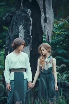 Jovem casal de elfos ao ar livre agaist morrendo de árvore queimada
