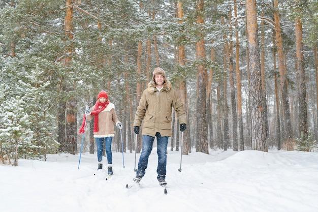 Jovem casal de esqui na floresta de inverno