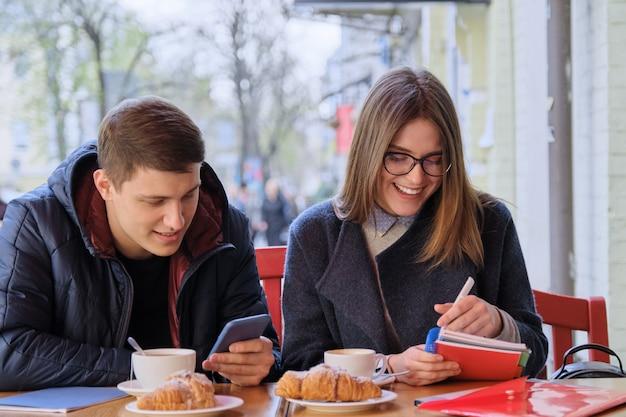 Jovem casal de estudantes estuda no café ao ar livre