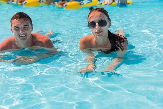 Jovem casal de férias deitado na piscina do resort e aproveitando o dia ensolarado de verão
