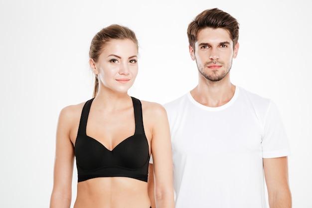 Jovem casal de fitness em pé isolado